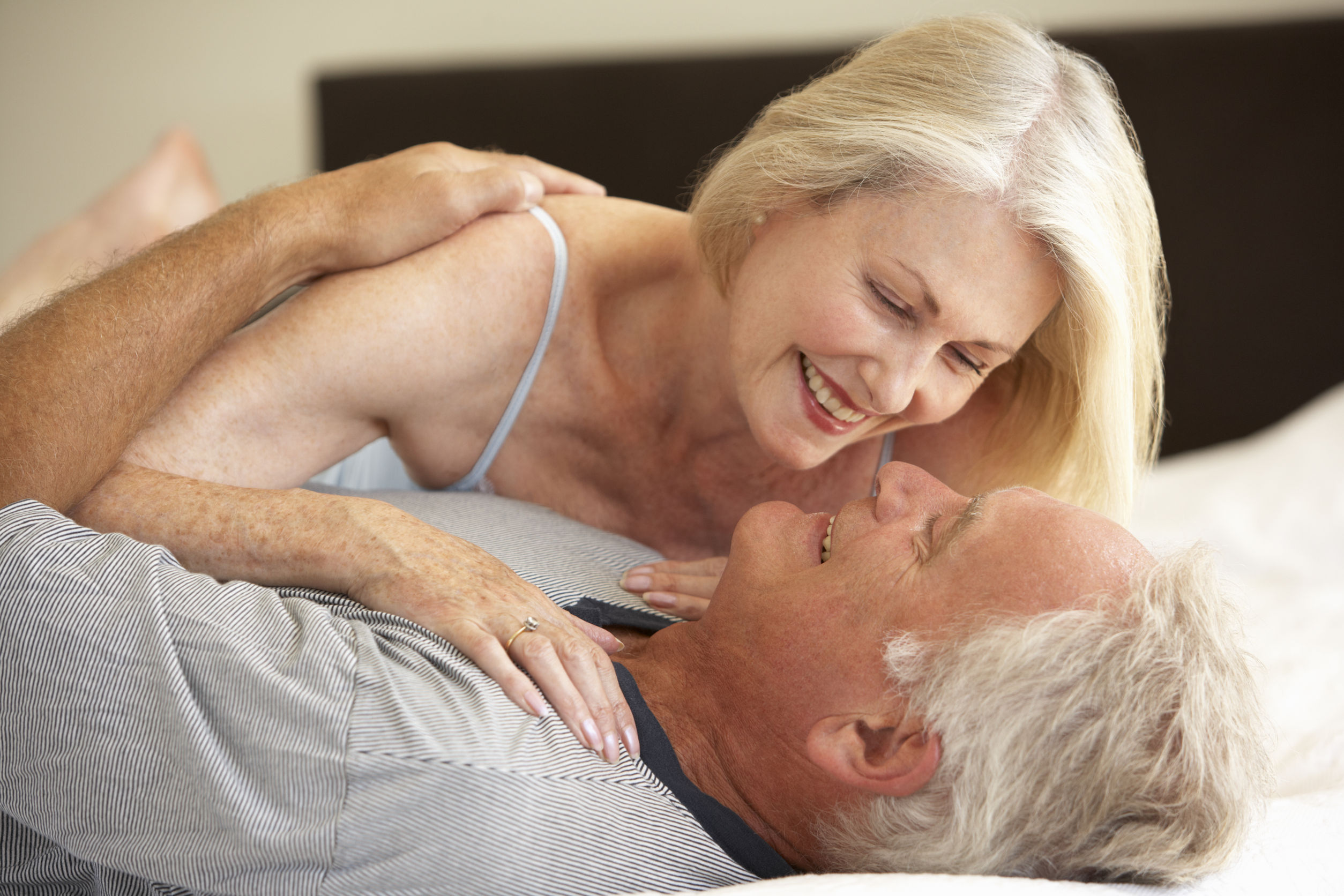 elderly couple smiling at each other while lying in bed